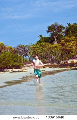 Young Boy With Red Hair In Swimsuit Is Running Along The Beautiful Beach