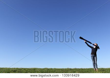 Young girl with telescope watching the sky
