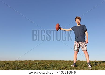 Teenage boy holding a football outside in a meadow