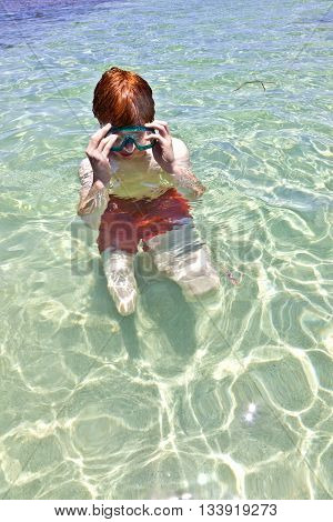boy with diving mask swimming in the clear ocean