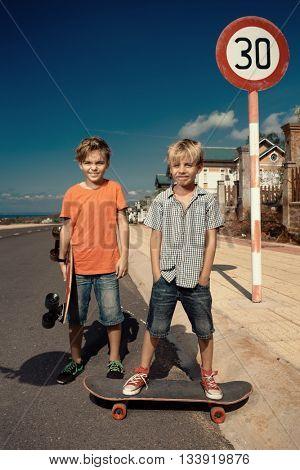 Little boys on longboard skate
