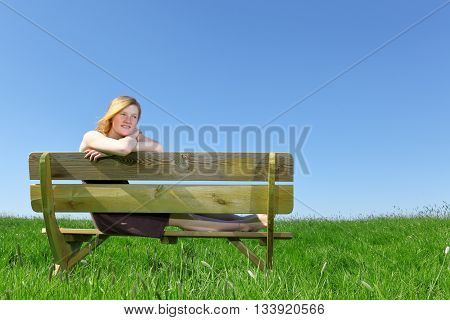 Happy young girl sitting on a bench in summer