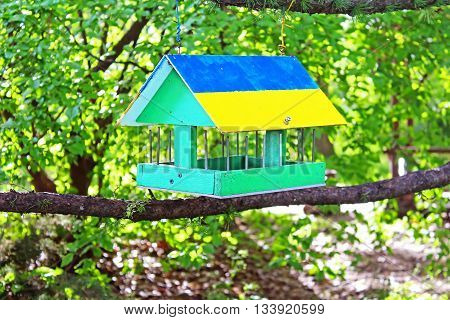 Bird feeder painted as Ukrainian flag in the summer forest