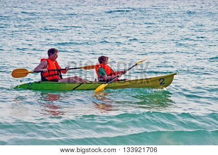 Father And Son Padelling With A Canoe On Open Sea