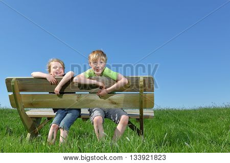 Two happy young kids sitting on a bench in summer