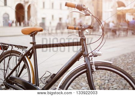 Isolated vintage bicycle with urban cityscape in the background