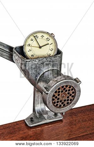 Alarm clock in manual meat grinder on white background.Toned image.