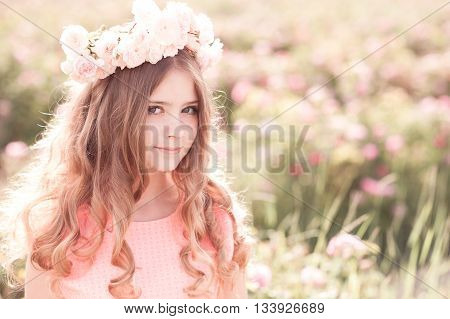 Smiling blonde girl 14-16 year old posing with roses wreath outdoors. Looking at camera.