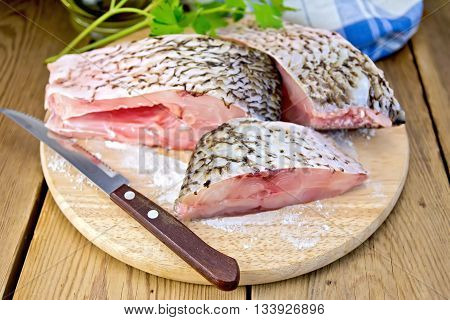 Bream raw sliced slices, parsley, towel and knife on a wooden boards background