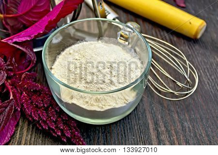 Amaranth flour in a glass cup with a mixer, a rolling pin and sieve, purple amaranth flower on a background of wooden boards