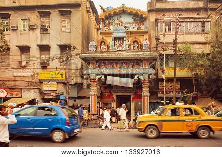 KOLKATA, INDIA - JAN 10, 2016: People walk past the Hindu temple at the street with powerfull traffic road with taxi and cars on January 10, 2016. Kolkata has a density of 814.80 vehicles per km road length