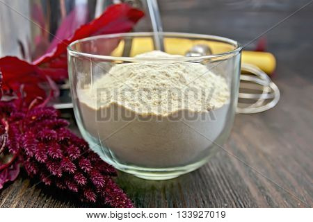 Amaranth flour in a glass cup with a mixer, purple amaranth flower on a background of wooden boards