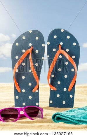 Flip Flops In The Sand With Sunglasses And A Beach Towel