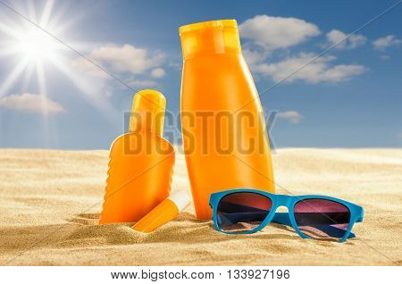 Various sunsreen products in the sand on the beach