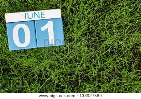 June 1st. Image of june 1 wooden color calendar on green lawn grass background. First summer day.