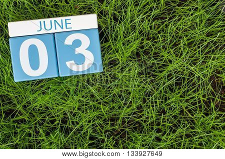 June 3rd. Image of june 3 wooden color calendar on green lawn grass background. Summer day.