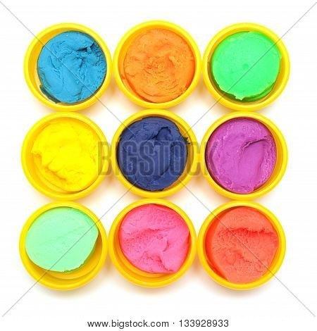 Containers with colorful plasticine on white Background