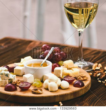 Cheese Board Served With Grapes, Nuts And A Glass Of White Wine On A Wooden Background