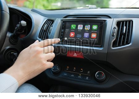 Alushta Russia - May 31 2016: Man hand touching to the home screen multimedia system with Car Play. Car Play was created and developed by the Apple inc.