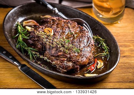 Healthy lean grilled medium-rare steak and vegetables with whiskey glass and a spice in a rustic pub or tavern. Food-styling