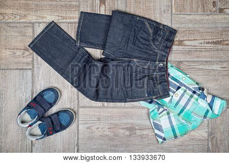 Flat lay picture of boy's casual outfit. Boy's casual outfit on wood board background