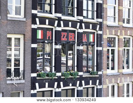 Pizzeria in an old house at a canal. Old houses of Amsterdam.
