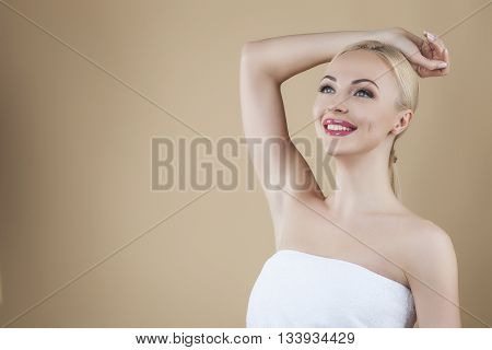 Beautiful young woman touching her head isolated on brown background, posing studio