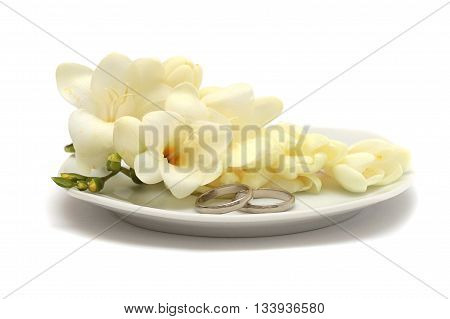 Two wedding platinum rings and flowers on a white plate
