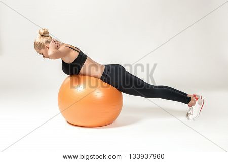 Young blonde woman training with fitball. Fitness exercises for abdomen