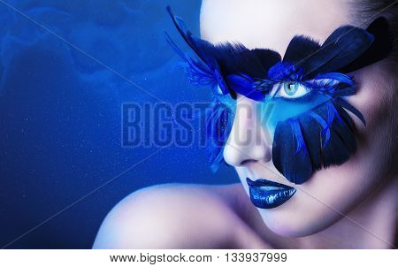 Beautiful woman with make-up with blue feathers on a blue background