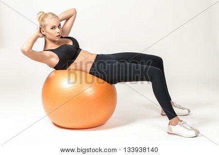 Young blonde woman training with fitball. Fitness exercises for abdomen. ooks into the camera