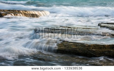 Powerful waves crashing with power on sea rock plates creating small waterfalls and smooth streams of water.