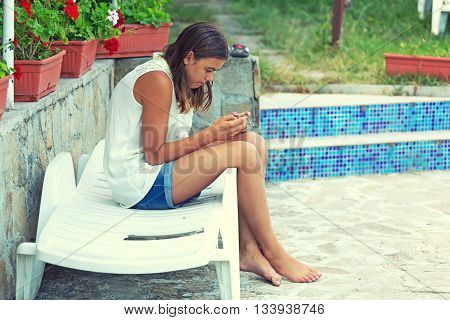 Teen girl listening to music and looking at the phone