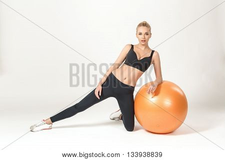 Young blonde woman training with fitball. Fitness exercises. she looks into the camera