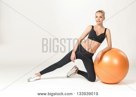 Young blonde woman training with fitball. Fitness exercises
