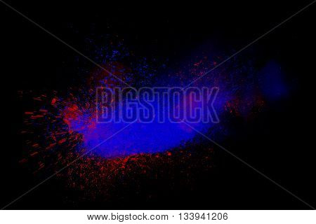 Freeze motion of red and blue powder exploding isolated on black dark background. Abstract design of dust cloud. Particles explosion screen saver wallpaper with copy space. Vivid colorful ash
