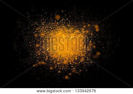 Freeze motion of colorful yellow powder exploding isolated on black dark background. Abstract design of color dust cloud. Particles explosion screen saver wallpaper brush. Universe creation concept