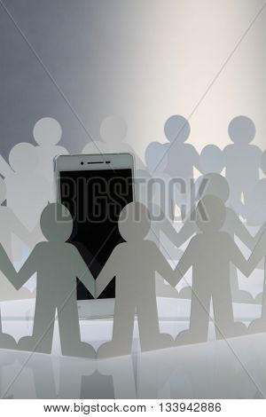 Paper people standing together hand in hand surround a smart phone. the power of social media