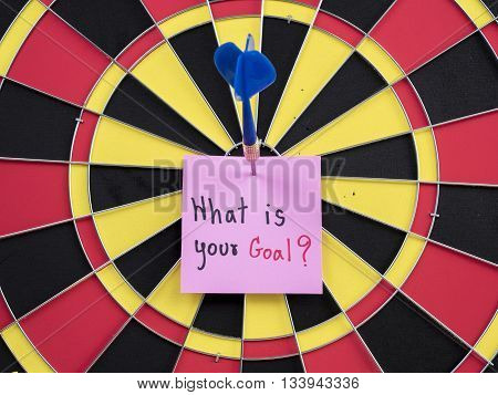 Handwriting What is your goal on noteper with dart arrow and dart board. (Business concept)