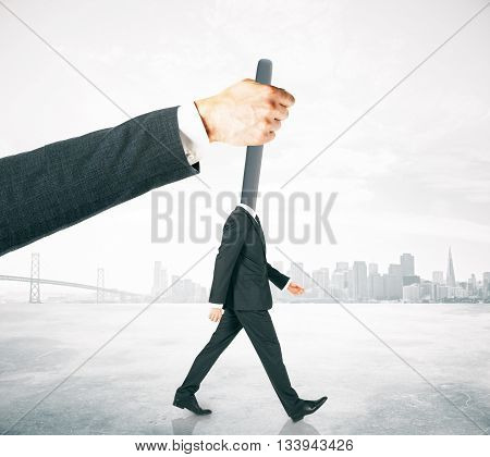 Hand manipulating lever-headed businessman on abstract foggy city background. Concept of control