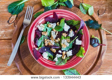 Salad: beet salad with feta cheese and walnuts on wooden background.