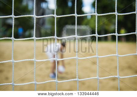 Beach soccer player through the net. Olympic games.
