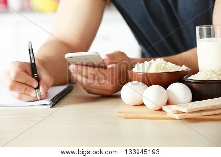 Man counting calories on table