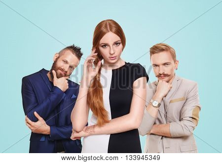 Love triangle. Young beautiful woman choose from to handsome men isolated at blue. Hard choice, lover, husband. Adultery, relationship issue, love problem concept. Girl think who to choose.