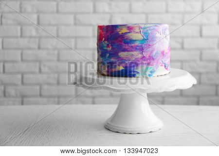 Colorful frosted cake on white brick background