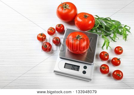 Tomatoes with digital kitchen scales on wooden background