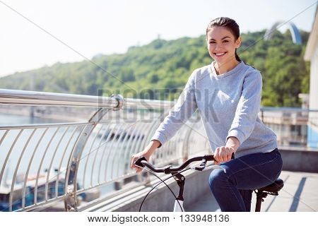 Good day for riding. Smiling beautiful young woman riding a bike on the quay in the city