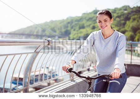 Feeling happiness. Smiling young woman looking at camera and holding handles of a bicycle