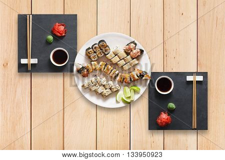 Japanese food restaurant, sushi maki gunkan unagi roll plate or platter set. Set for two with chopsticks, ginger, soy, wasabi. Sushi at black stone and wooden planks background. Top view, flat lay.