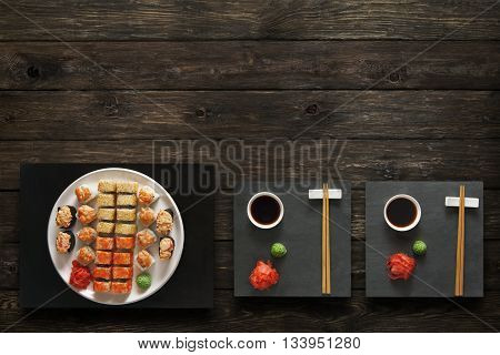 Japanese food restaurant, salmon sushi maki gunkan roll plate or platter set. Set for two with chopsticks, ginger, soy, wasabi. Sushi at black stone mat and rustic wood background. Top view, flat lay.
